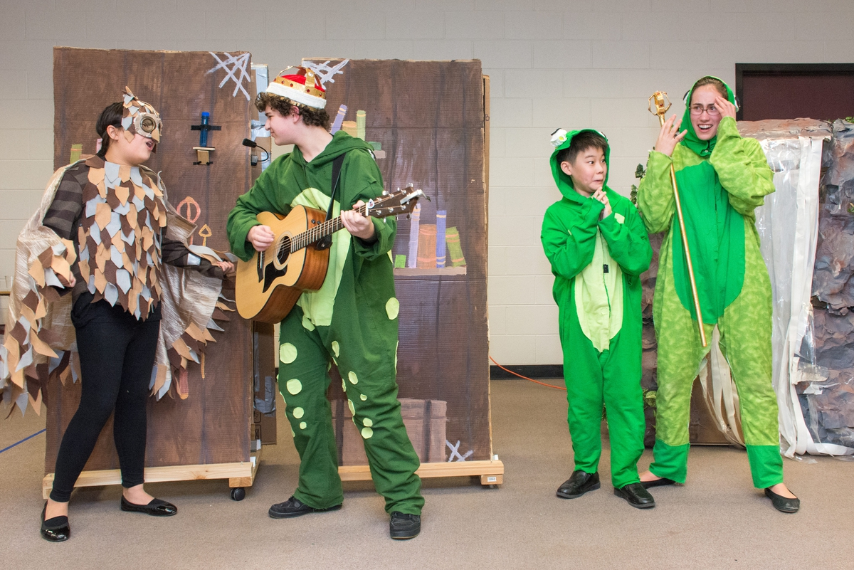 Students performing at a tournament dressed as frogs and an owl