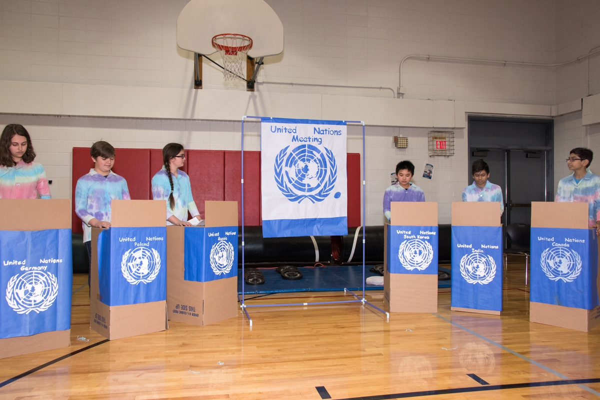 "Students performing a ""mock"" United Nations Meeting, at a tournament"